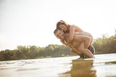 счастливая женщина езды piggyback человека соедините влюбленность стоковое изображение