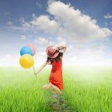 Счастливая женщина держа воздушные шары в желтых поле риса и небе облака Стоковая Фотография