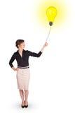 Счастливая женщина держа воздушный шар электрической лампочки Стоковые Изображения