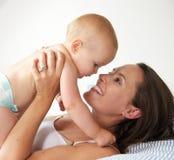 Счастливая женщина держа младенца и усмехаясь в кровати стоковые изображения rf