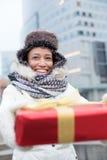 Счастливая женщина держа подарок во время зимы в городе Стоковая Фотография RF