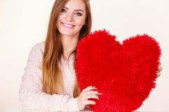 Счастливая женщина держа подушку сердца форменную Стоковые Изображения RF