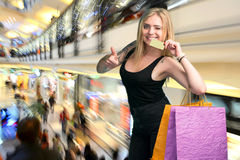 Счастливая женщина держа хозяйственные сумки и кредитную карточку Стоковая Фотография