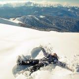 Счастливая женщина делая ангела снега в снеге Стоковое Изображение