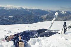 Счастливая женщина делая ангела снега в снеге Стоковые Изображения RF
