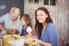 Счастливая женщина имея завтрак с семьей стоковое изображение
