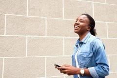 Счастливая женщина используя мобильный телефон смотря прочь Стоковая Фотография RF
