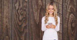 Счастливая женщина используя умный телефон против деревянной стены иллюстрация штока