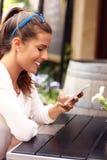 Счастливая женщина используя smartphone в кафе Стоковые Фото