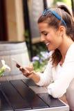 Счастливая женщина используя smartphone в кафе Стоковые Изображения