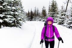 Счастливая женщина идя в древесины зимы с рюкзаком Стоковые Изображения RF