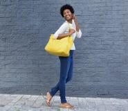 Счастливая женщина идя и говоря на мобильном телефоне Стоковое Изображение