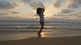 Счастливая женщина идя и закручивая на пляж около океана Молодая красивая девушка наслаждаясь жизнью и имея потеху на море Стоковое Изображение RF