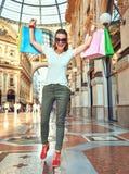 Счастливая женщина моды в eyeglasses с радоваться хозяйственных сумок стоковые фото
