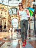 Счастливая женщина моды с хозяйственными сумками указывая на что-то стоковое изображение