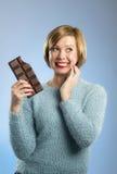Счастливая женщина наркомана шоколада держа большой рот бара запятнанное и шальное excited выражение стороны Стоковая Фотография