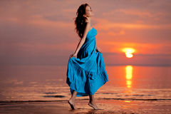 Счастливая женщина наслаждаясь в заходе солнца моря Стоковые Изображения RF