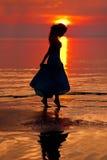 Счастливая женщина наслаждаясь в заходе солнца моря Silhouetted против солнец Стоковые Фотографии RF