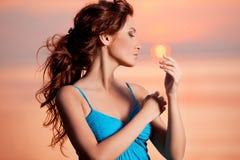 Счастливая женщина наслаждаясь в заходе солнца моря Silhouetted против солнец Стоковое Изображение