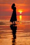 Счастливая женщина наслаждаясь в заходе солнца моря Silhouetted против солнец Стоковое Фото