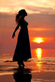 Счастливая женщина наслаждаясь в заходе солнца моря Silhouetted против солнец Стоковые Изображения