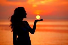 Счастливая женщина наслаждаясь в заходе солнца моря Silhouetted против солнец Стоковое фото RF