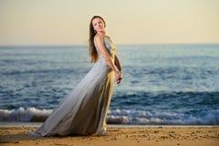 Счастливая женщина наслаждаясь заходом солнца на пляже Стоковые Фотографии RF