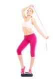 Счастливая женщина на веся масштабе Потеря веса диеты стоковые изображения