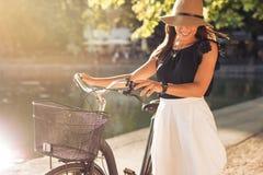 Счастливая женщина на парке с велосипедом Стоковые Фотографии RF
