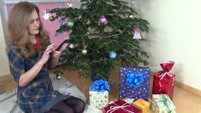 Счастливая женщина около рождественской елки звонит телефонный звонок smartphone сток-видео