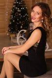 Счастливая женщина около рождественской елки Стоковое Фото