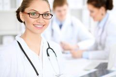 Счастливая женщина доктора с медицинским персоналом на больнице сидя на таблице Красные стекла рамки Стоковые Фотографии RF