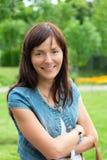 Счастливая женщина ослабляя в парке Красивейшая молодая женщина outdoors насладитесь природой Здоровая усмехаясь девушка на предп Стоковое фото RF