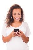 Счастливая женщина отправляя СМС на ее телефоне стоковая фотография