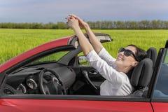 Счастливая женщина отдыхая за рулем автомобиля на проселочной дороге на заходе солнца Стоковая Фотография