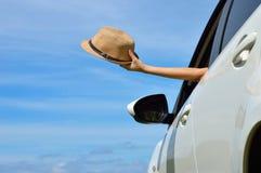 Счастливая женщина показывает шляпу солнца от окна автомобиля Стоковое Изображение