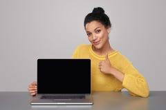 Счастливая женщина показывая пустой черный экран comuter стоковое фото rf
