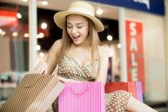 Счастливая женщина покупок смотря ее приобретение стоковые изображения rf