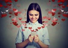 Счастливая женщина посылая сообщение влюбленности на сердцах мобильного телефона летая прочь Стоковое фото RF