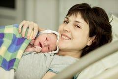 Счастливая женщина после рождения с newborn младенцем Стоковые Изображения RF