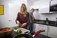 Счастливая женщина подготавливая еду при человек стоя в предпосылке на кухне Стоковая Фотография