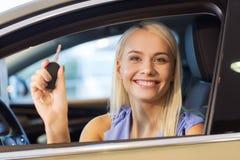 Счастливая женщина получая ключ автомобиля в автосалоне или салоне Стоковые Изображения RF