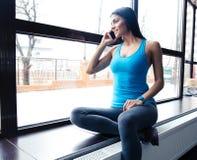 Счастливая женщина пригонки говоря на телефоне Стоковое Изображение RF