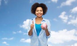 Счастливая женщина при копилка показывая большие пальцы руки вверх Стоковое Изображение