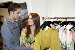 Счастливая женщина при парень смотря один другого в бутике одежды моды Стоковые Изображения RF