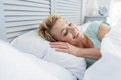 Счастливая женщина просыпая вверх в кровати Стоковое Изображение
