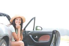 Счастливая женщина сидя в автомобиле с откидным верхом против ясного неба Стоковые Фото