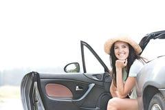 Счастливая женщина сидя в автомобиле с откидным верхом против ясного неба Стоковые Фотографии RF