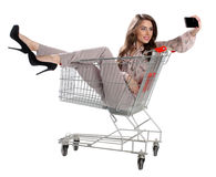 Счастливая женщина сидя в вагонетке покупок и делает фото Стоковая Фотография