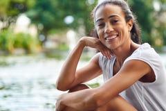 Счастливая женщина сидя в парке около пруда Стоковое Изображение